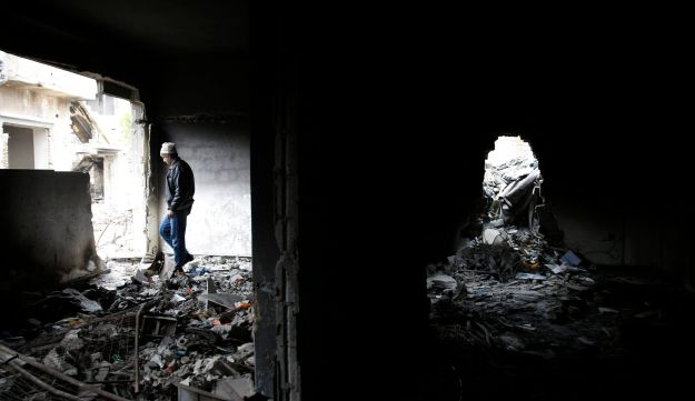 A man checks his destroyed house in a devastated part of the old city, in Homs, Syria, Wednesday, Jan. 17, 2018.