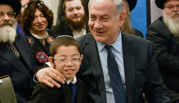 Prime Minister Benjamin Netanyahu embraces the boy Moshe Holtzberg, whose parents died in the 2008 attack no a Mumbai chabad center.