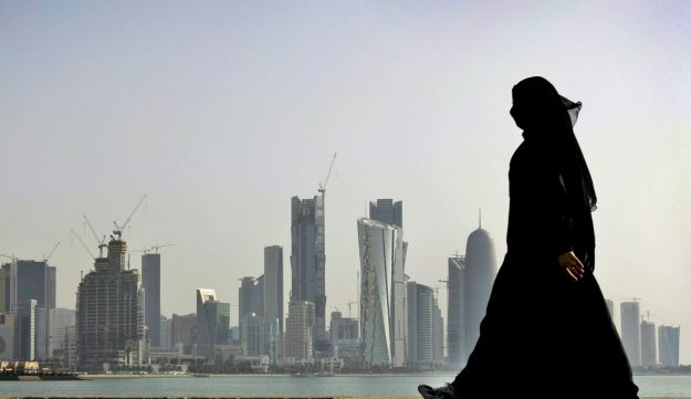A Qatari woman walking in front of the city skyline in Doha, Qatar.