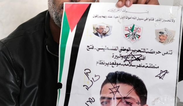 Firas Tamimi holds up the defaced mourning notice.