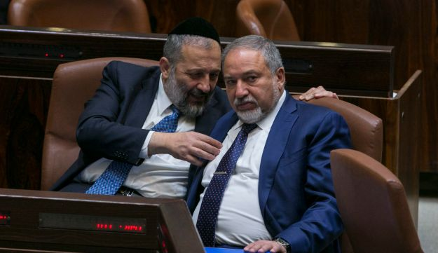 Interior Minister Arye Dery speaks with Defense Minister Avigdor Lieberman at the Knesset, October 23, 2017.