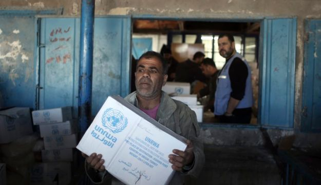 Palestinians receive food aid at a U.N. Relief and Works Agency (UNRWA) warehouse in the Shati refugee camp, Gaza City, as the U.S. administration announced it is cutting funding to to the UN agency. Jan. 14, 2018