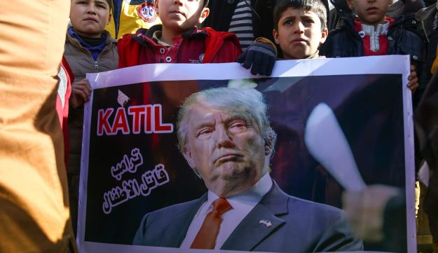 "Syrians hold up a banner with the word ""Killer"" in Turkish and the Arabic phrase ""Trump is a killer of children"" during a demonstration in northern Syria on January 19, 2018,"