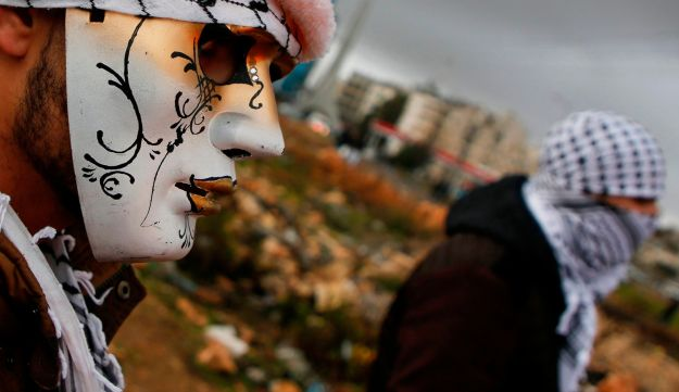 A Palestinian protester wears a mask during clashes with Israeli forces on the outskirts of the West Bank city of Ramallah, near the Jewish settlement of Beit El. January 23, 2018