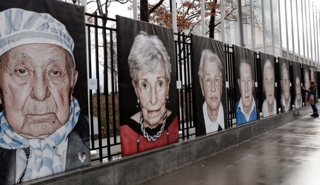 Portraits of Holocaust survivors by Italian photographer Luigi Toscano line a fence bordering United Nations headquarters,  Jan. 23, 2018, in New York