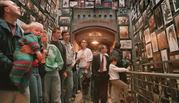 Visitors to the U.S. Holocaust Memorial Museum in Washington studying photos from the village of Ejszyszki, Lithuania.