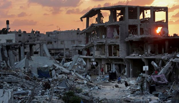 Palestinians walk during the sunset between the rubble of their destroyed building in Shijaiyah neighborhood of Gaza City in the northern Gaza Strip, Sunday, Oct. 12, 2014.