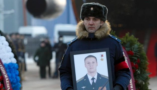 A Russian officer of a portrait of Maj. Filipov at a farewell service. Chkalovsky military airport, Russia, February 8, 2018.