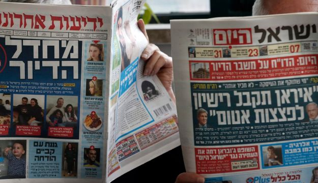 Two men reading Israeli dailies Yedioth Ahronoth, left, and Israel Hayom in Jerusalem, February 2015.