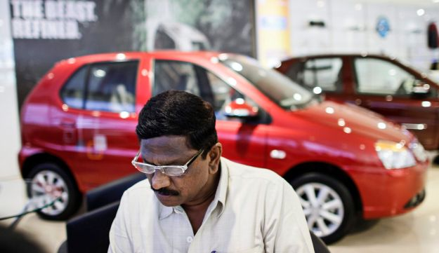 A customer sits in front of a red Tata Motors Ltd. automobile on display at a dealership in Mumbai, India.