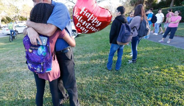 Family member embrace following a shooting at Marjory Stoneman Douglas High School, Parkland, Florida, February 14, 2018.