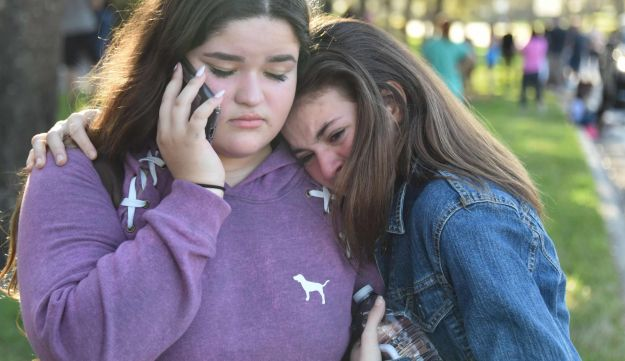 Students react following a shooting at Marjory Stoneman Douglas High School in Parkland, Florida, February 14, 2018.