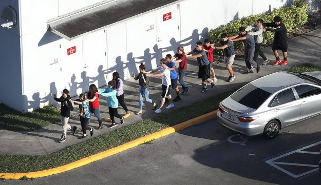 People are brought out of the Marjory Stoneman Douglas High School after school shooting, February 14, 2018 in Florida.