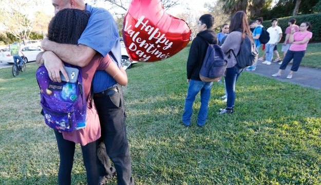 Family member embrace following a shooting at Marjory Stoneman Douglas High School, in Parkland, Florida, February 14, 2018.