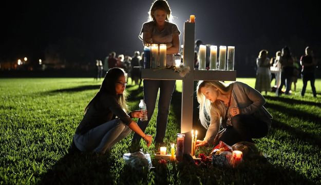 Maria Reyes, Stacy Buehler and Tiffany Goldberg light candles around a cross as they attend a candlelight memorial service for the victims of the shooting at Marjory Stoneman Douglas High School that killed 17 people on February 15, 2018 in Parkland, Florida.