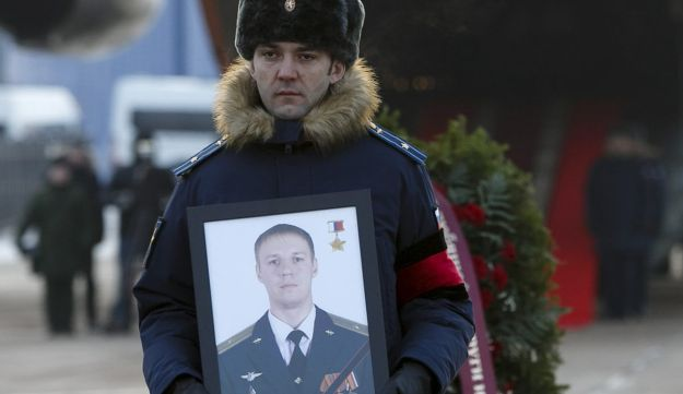 A serviceman holds a portrait of Russian air force pilot Roman Fillipov, who was killed after his aircraft was shot down over rebel-held territory in Syria, February 8, 2018.