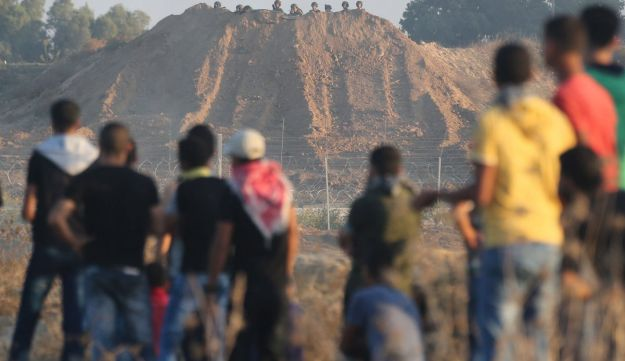 Palestinian protesters are seen as Israeli soldiers take cover behind a sand hill during clashes near the border between Israel and Central Gaza Strip October 15, 2015.