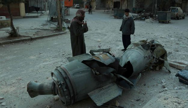 Syrian men walk past the remains of a rocket in rebel-held Douma in eastern Ghouta following airstrikes by regime forces, February 23, 2018.