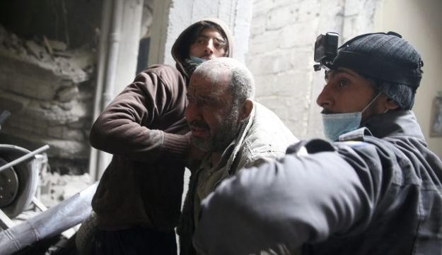 Civil defense help a man from a shelter in the besieged town of Douma in eastern Ghouta in Damascus, Syria, February 22, 2018.