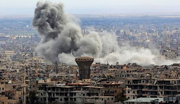 """A general view taken from Damascus shows smoke rising from the rebel-held enclave of Eastern Ghouta following fresh air strikes and rocket fire on February 27, 2018.  A fledgling """"humanitarian pause"""" announced by Russia in Syria's rebel-held enclave of Eastern Ghouta was rattled by fresh air strikes and rocket fire, several sources said."""