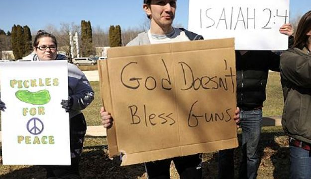 Anti-gun protesters stand outside the church