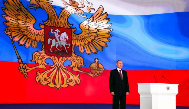 Russian President Vladimir Putin stands after giving his annual state of the nation address in Manezh in Moscow, Russia, Thursday, March 1, 2018