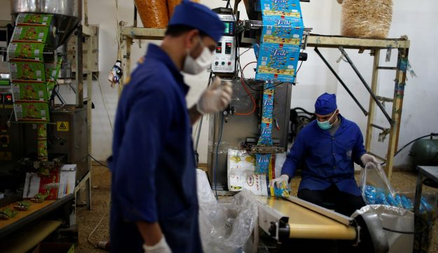 Palestinians work at Wael Al-Wadiya's snacks and chips factory, east of Gaza City February 19, 2018. Picture taken February 19, 2018. REUTERS/Mohammed Salem