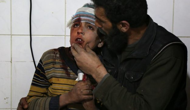 A wounded Syrian child is comforted by a man following a reported air strike by Syrian government forces in Kafr Batna, in eastern Ghouta, March 5, 2018.
