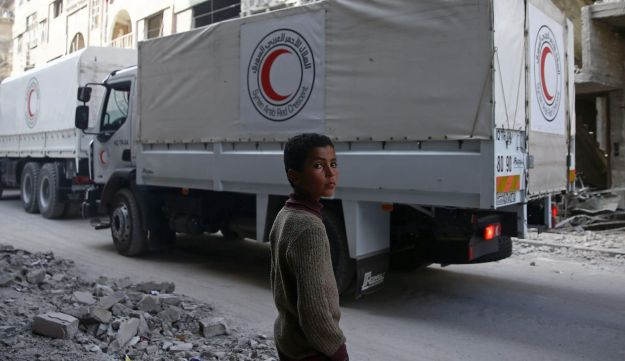 A boy stands as an aid convoy of Syrian Arab Red Crescent drives through the besieged town of Douma, eastern Ghouta, Syria, March 5, 2018.