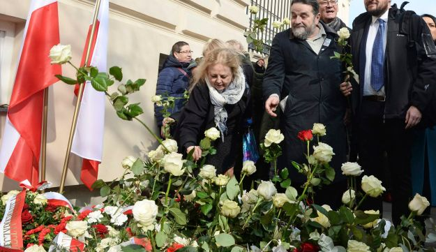 People lay flowers during ceremonies marking the 50th anniversary of student protests that were exploited by the communists to purge Jews from Poland, at the Warsaw University in Warsaw, Poland, March 8, 2018.