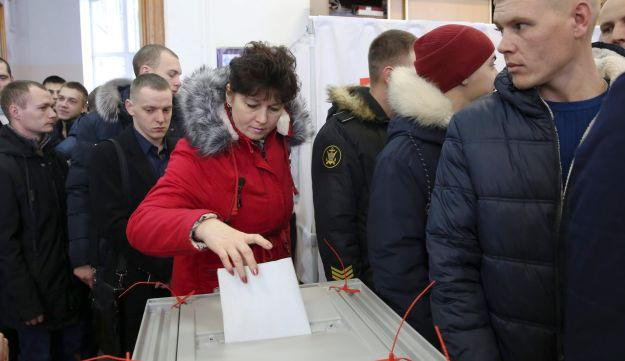 A woman casts her ballot as other people line up to get their ballots at a polling station in the Russian Far Eastern port city of Vladivostok, March 18, 2018.