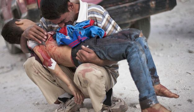 A Syrian man cries while holding the body of his son near Dar El Shifa hospital in Aleppo, Syria. Oct. 3, 2012