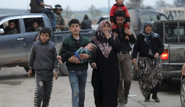 A kurdish boy holds his baby brother, as he walks with his family in Afrin, Syria March 18, 2018