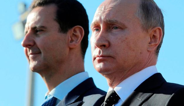 Russian President Vladimir Putin, right, and Syrian President Bashar Assad watching troops march at the Hemeimeem air base in Syria