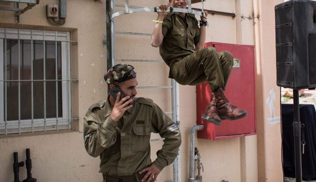 An Israeli soldier uses a cell phone on a base, March 25, 2016.