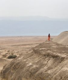 The Great Rift Valley: Dead Sea section. Photo shows woman in orange skirt and red top, dark hair, her back to the camera, standing on a cliffside in Israel, overlooking the Dead Sea valley. In the distance, almost hidden in haze, we see the mountains in Jordan.
