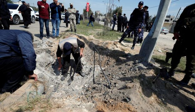 FILE PHOTO: Palestinians inspect the site of an explosion that targeted a convoy that was carrying Palestinian Prime Minister Rami Hamdallah in Gaza, March 13, 2018.