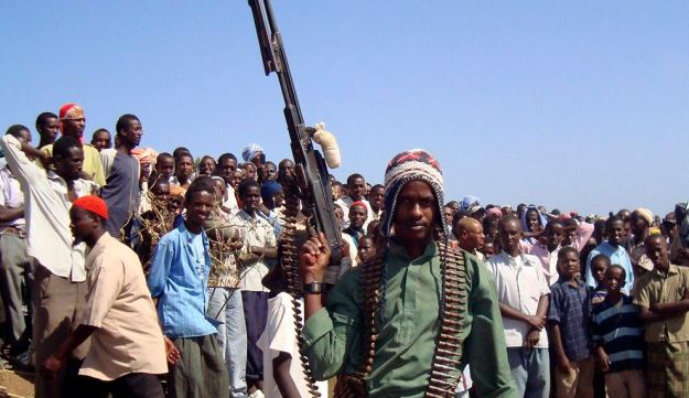 An Islamist fighter poses with his weapon as he keeps the crowd at bay during an execution of a Somali, Ali Hussein, in Bulo Marer, Somalia. Dec.13, 2008