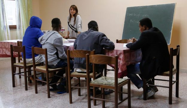 Teresa Puja, a teacher, addresses a group of refugees during an Italian lesson at the Palazzo Condo, a hostel for refugees in Satriano, Italy. Feb. 16, 2016