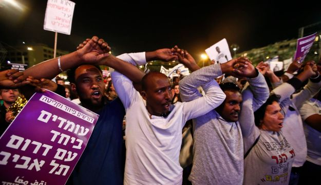 African asylum seekers and Israelis link arms during the protest against deportations in Tel Aviv, March 24, 2018.