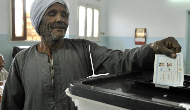 An Egyptian man casts his vote at a polling station in the ancient city of Luxor