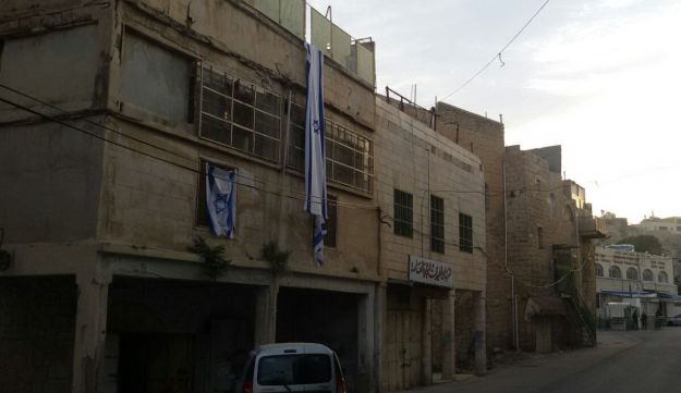 The abandoned home in Hebron, draped in an Israeli flag, March 27, 2018
