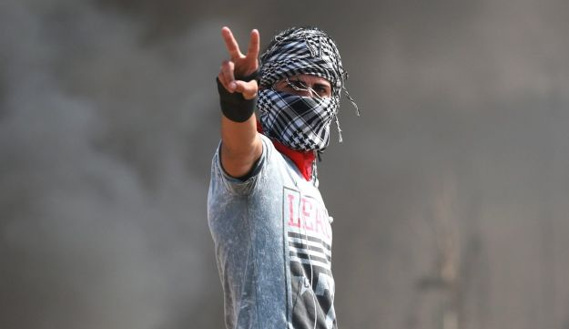A Palestinian protester gestures as smokes rises from a fire during clashes with Israeli troops near the Israeli border fence in the east of Gaza City October 10, 2015