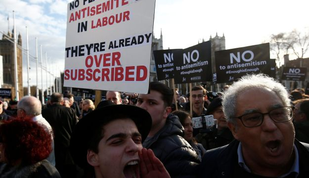 Protesters hold placards and flags during a demonstration, organised by the British Board of Jewish Deputies for those who oppose anti-Semitism, in Parliament Square in London, Britain, March 26, 2018.