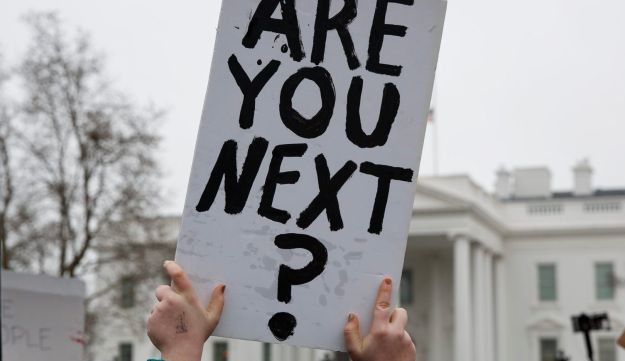 Demonstrators hold signs during a protest in favor of gun control reform in front of the White House, Feb. 19, 2018, in Washington D.C.
