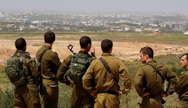 Israeli soldiers listen to a briefing on the Israeli side of the border with the northern Gaza Strip, Israel, March 29, 2018. REUTERS/Amir Cohen