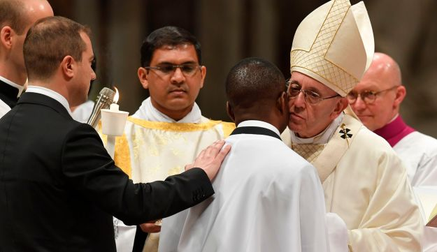 Pope Francis with Nigerian John Ogah next to his godfather Italian carabinieri Nunzio Carbone (L), during the Easter Vigil at St Peter's basilica on March 31, 201 in Vatican.