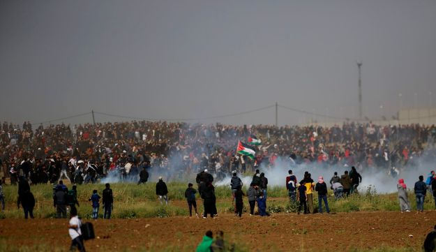 Israeli soldiers fire teargas canisters at Palestinians during a demonstration near the Gaza Strip border, March 30, 2018.