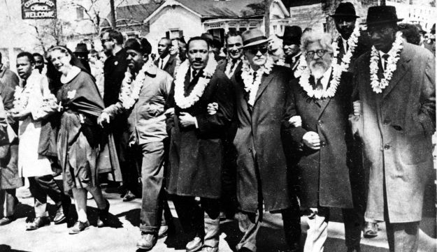 Dr. Martin Luther King Jr. links arms with other civil rights leaders as they begin the march to the state capitol in Montgomery from Selma, Ala. on March 21, 1965.