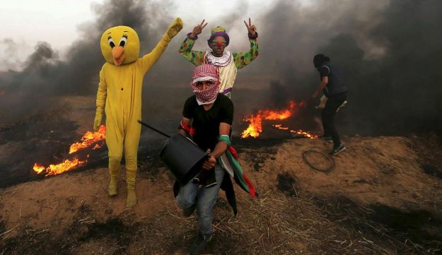 Palestinians wearing costumes are seen at the clashes scene at Israel-Gaza border in the southern Gaza Strip April 5, 2018